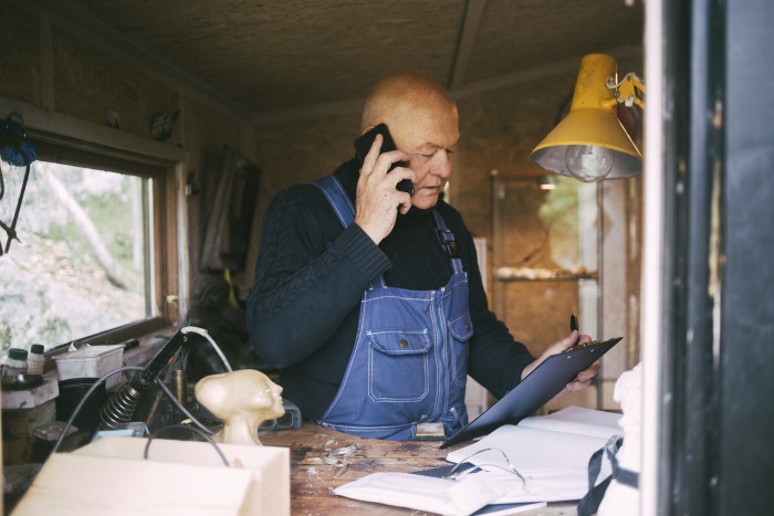 Senior businessman talking on mobile phone while looking at clipboard at garage
