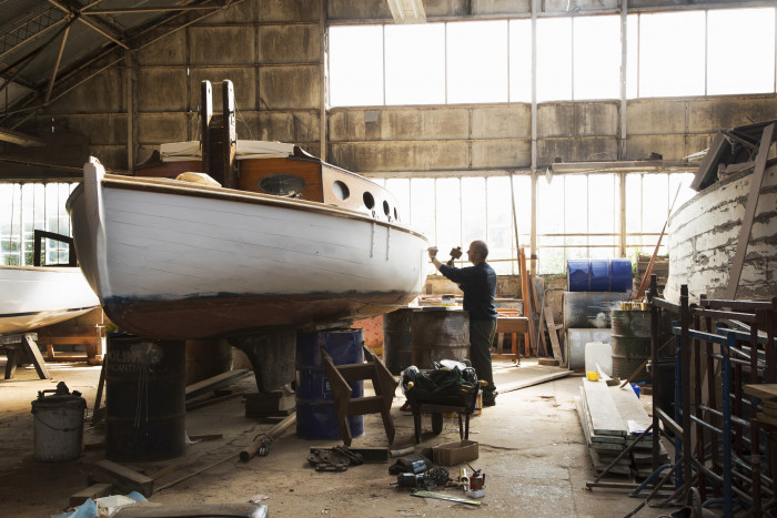 Skilled craftsman reconditioning old sailing boats in boat yard near Norfolk Broads UK.