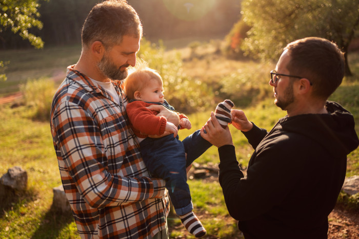 Gay couple with their baby boy in nature