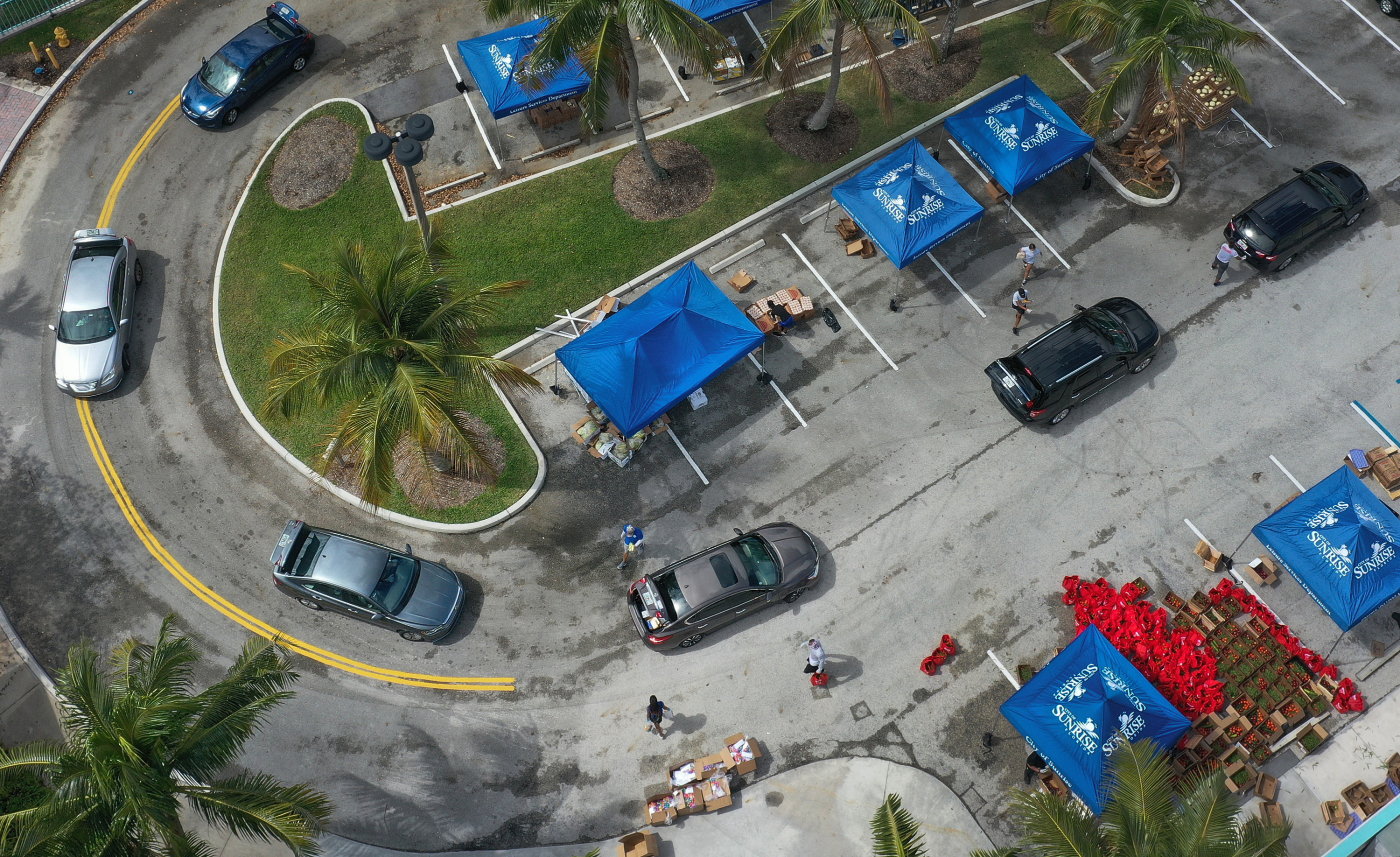 SUNRISE, FLORIDA - APRIL 06: An aerial view from a drone shows vehicles passing though as they receive food provided by the food bank Feeding South Florida and being given away by the City of Sunrise on April 06, 2020 in Sunrise, Florida. Feeding South Florida has seen a 600 percent increase in the those asking for food aid as people,some of whom have lost jobs, need to make ends meet during the coronavirus pandemic. The groceries being given away included milk, chicken, apples, tomatoes, cantaloupe as well as Easter eggs.  (Photo by Joe Raedle/Getty Images)