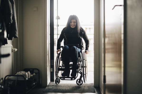 Full length of smiling young disabled woman entering home