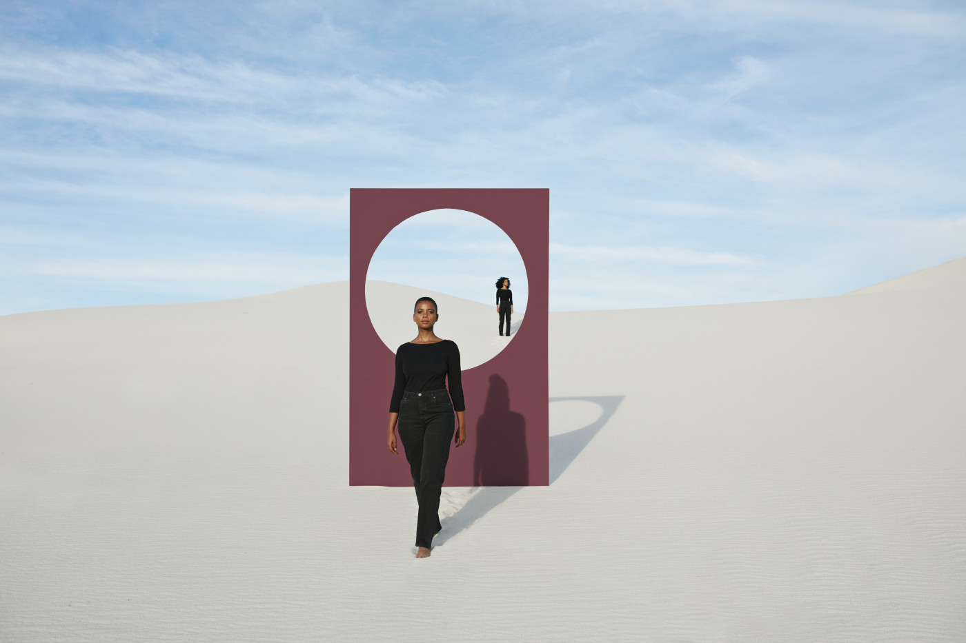 Young models with portal standing at desert against sky