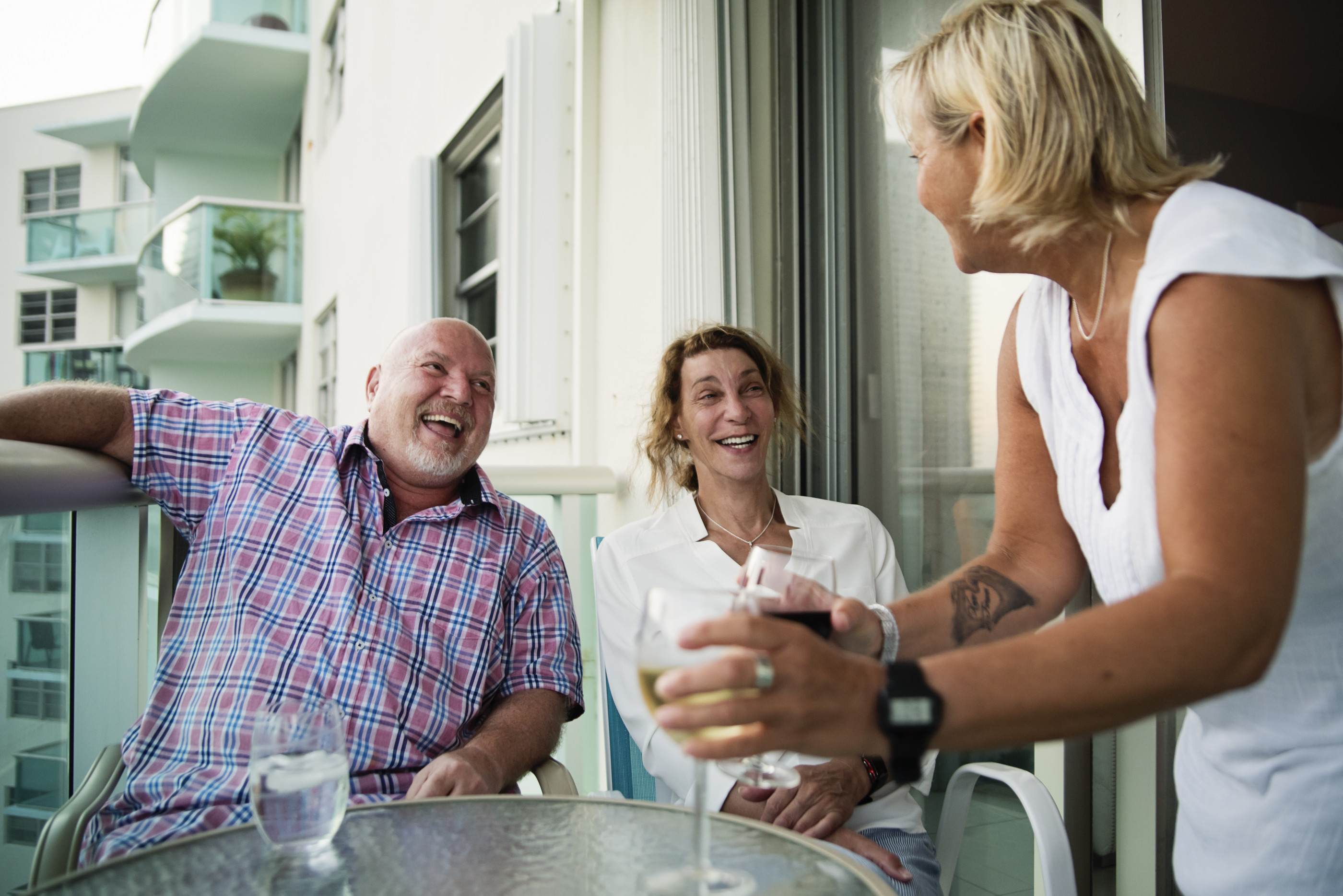 Group of mature LGBTQ friends at happy hour on balcony over the ocean. A lesbian couple, a gay man and a trans woman having a really good time together. Horizontal outdoors waist up shot with sun flare and copy space.