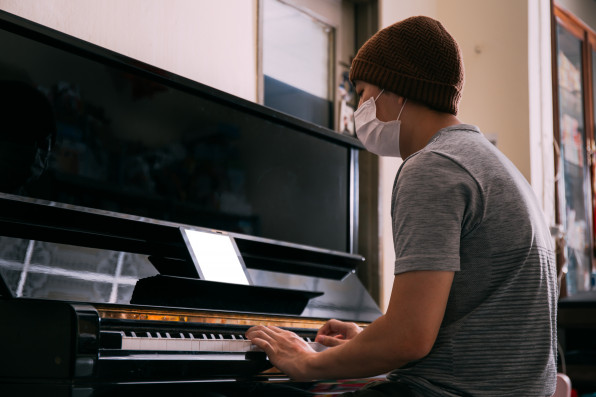 Young Asian male patient with sickness playing piano while using an empty copy space tablet screen at home