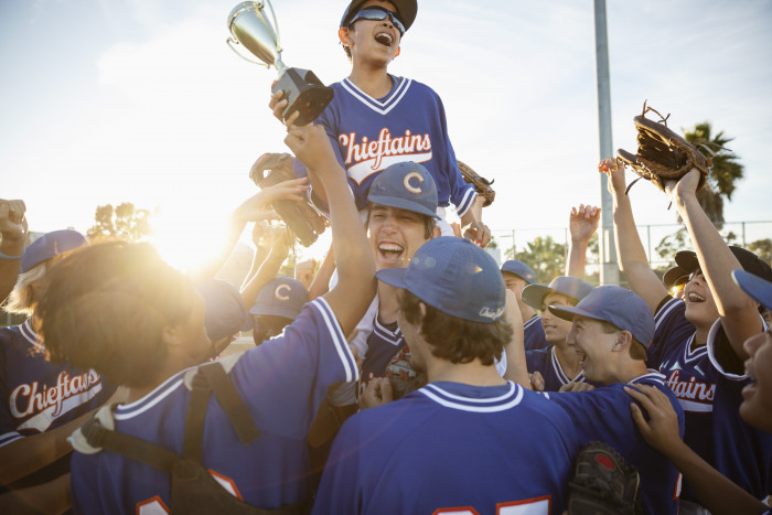 Excited baseball team with trophy celebrating