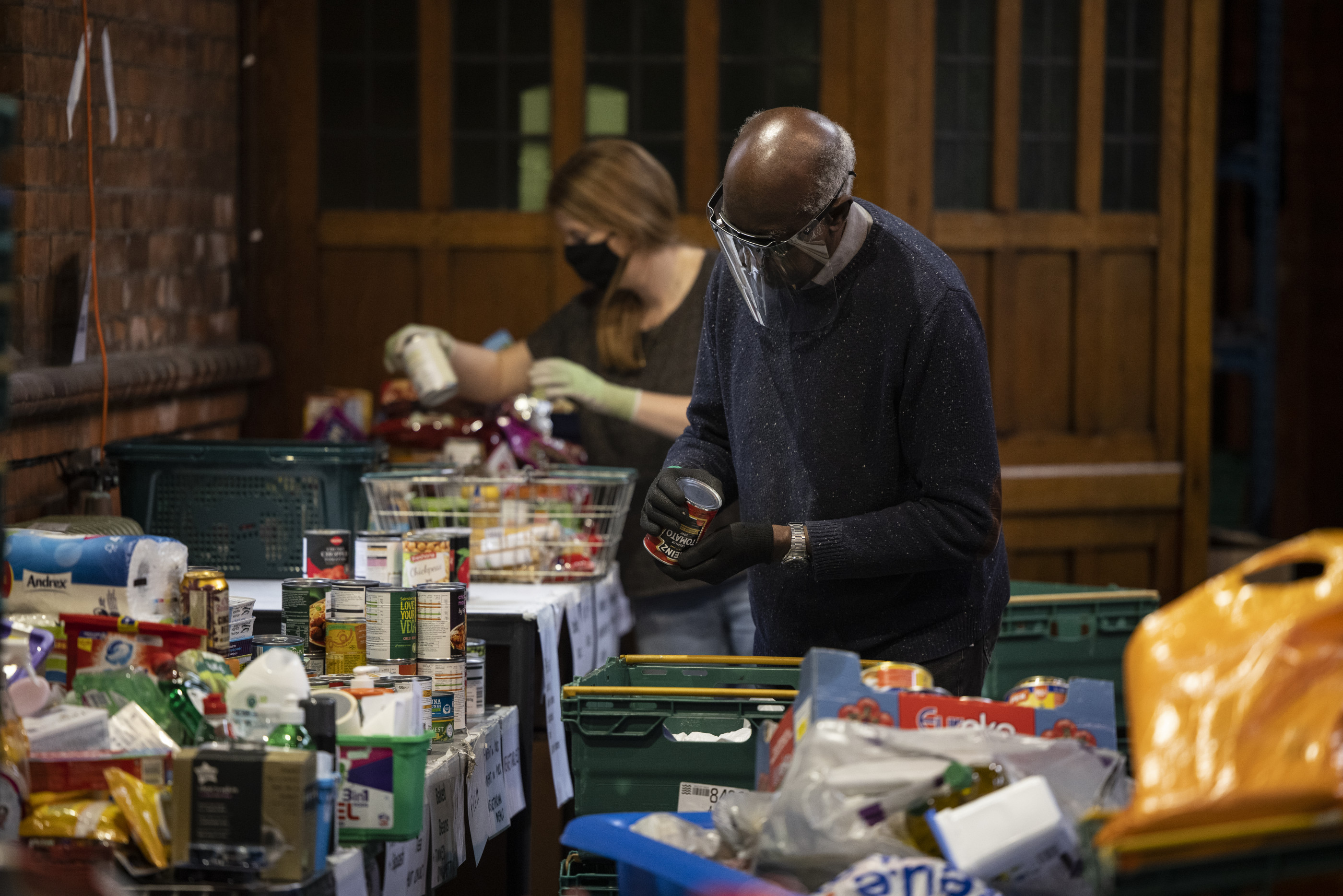 LONDON, ENGLAND - OCTOBER 27: Staff and volunteers pack and prepare food parcels at the South London warehouse and distribution centre at St Margaret's Church on October 27, 2020 in London, England. The South London warehouse is a distribution centre at St Margaret's Church, and part of the Lambeth network of foodbanks, a nationwide network supported by The Trussell Trust. Due to the ongoing Covid-19 crisis, the centre is operating a delivery service to those in need across South London. According to the Trussell Trust, there are around 14 million people are living in poverty in the UK, including 4.5 million children.  (Photo by Dan Kitwood/Getty Images)