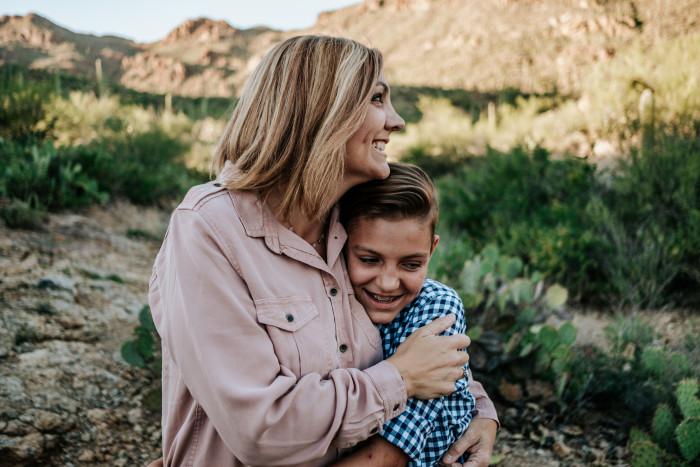 mother hugging smiling non binary child in the desert