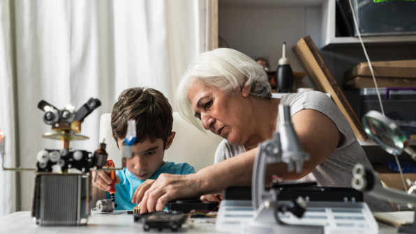 Little boy and grandmother working to build a robot. They are sitting on desk and using various gears. By is wearing a blue t-shirt while grandmother is wearing a gray blouse.