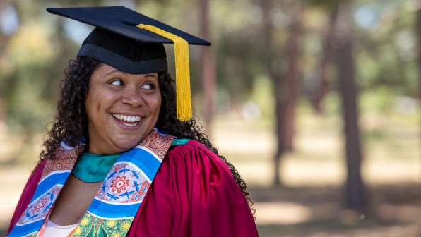 Close-up of a young female aboriginal student smiling dressed in her graduation gown.