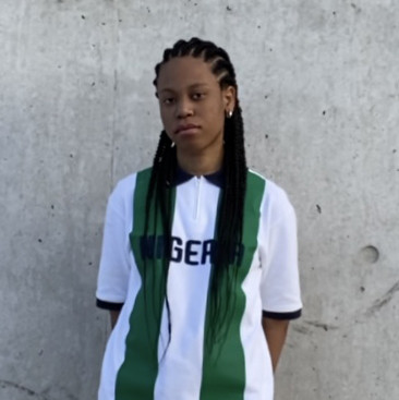 Isabel Okoro standing in front of a wall